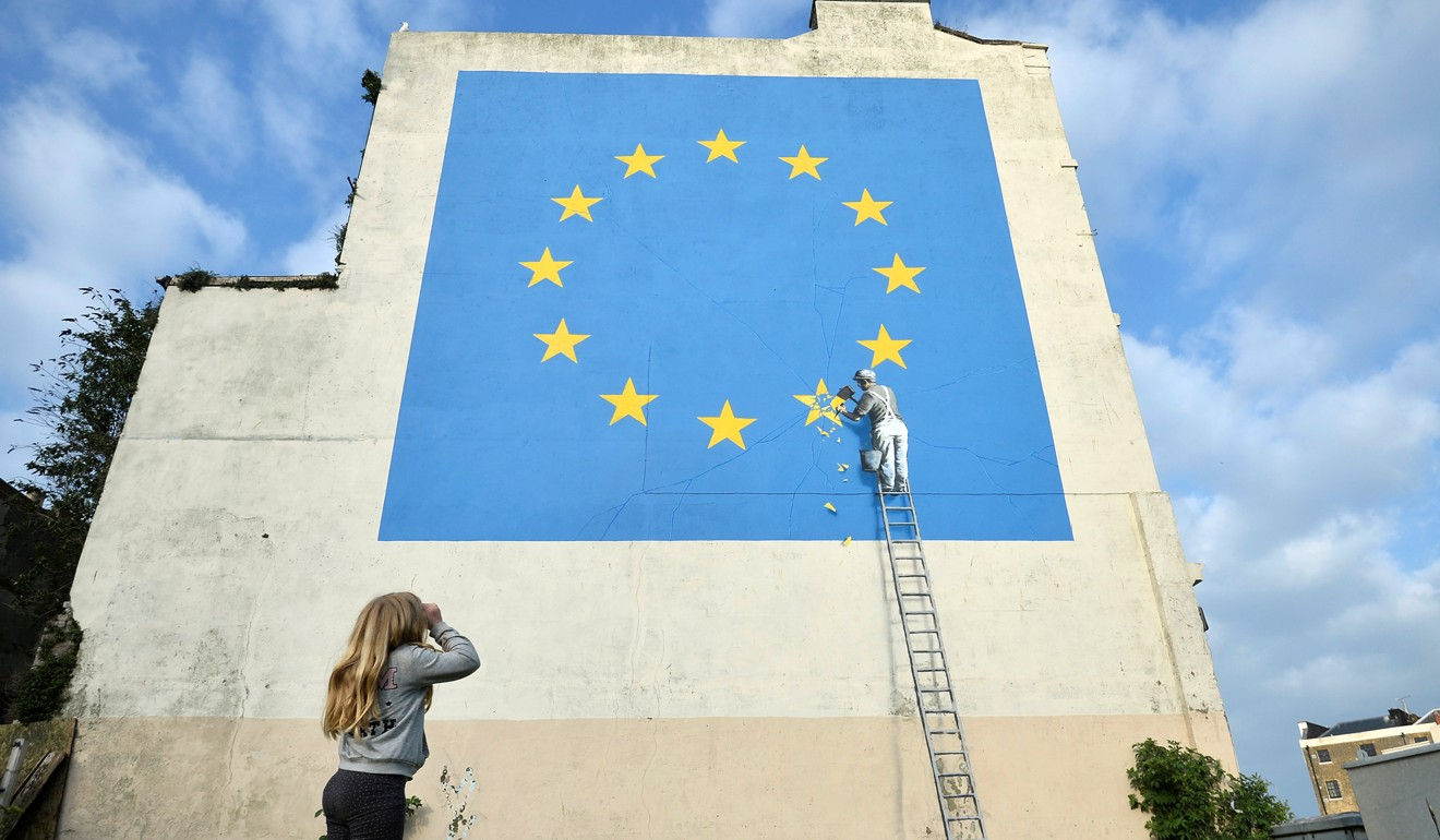 A girl looks at artwork attributed to street artist Banksy, depicting a workman chipping away at one of the 12 stars on the European Union, seen on a wall in the ferry port of Dover, Britain, on Sunday. Photo: Reuters