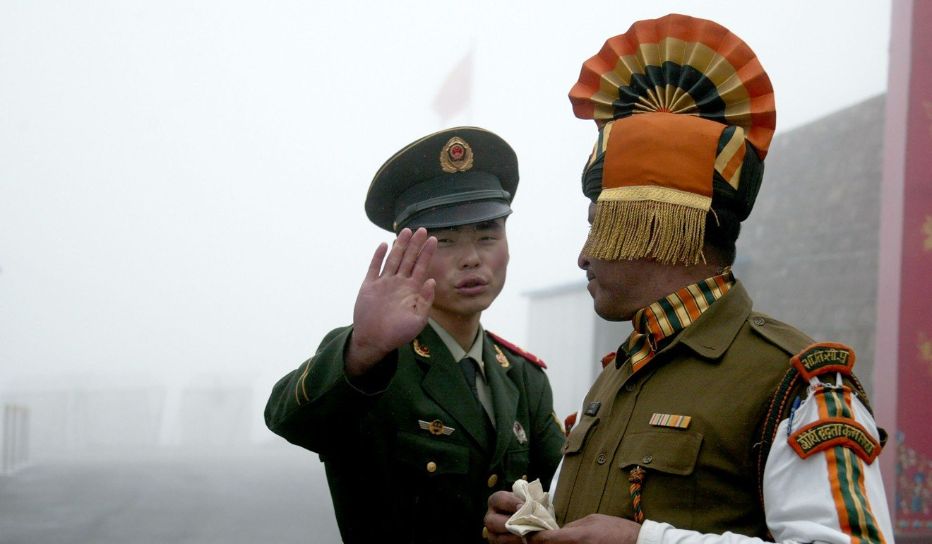 A Chinese soldier gestures to an Indian soldier at the Nathu La border crossing between India and China in India's northeastern Sikkim state. Photo: AFP