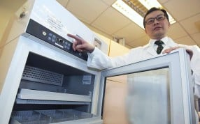 William Chui shows how vaccines should be stored in a special pharmacy fridge. Photo: Edward Wong