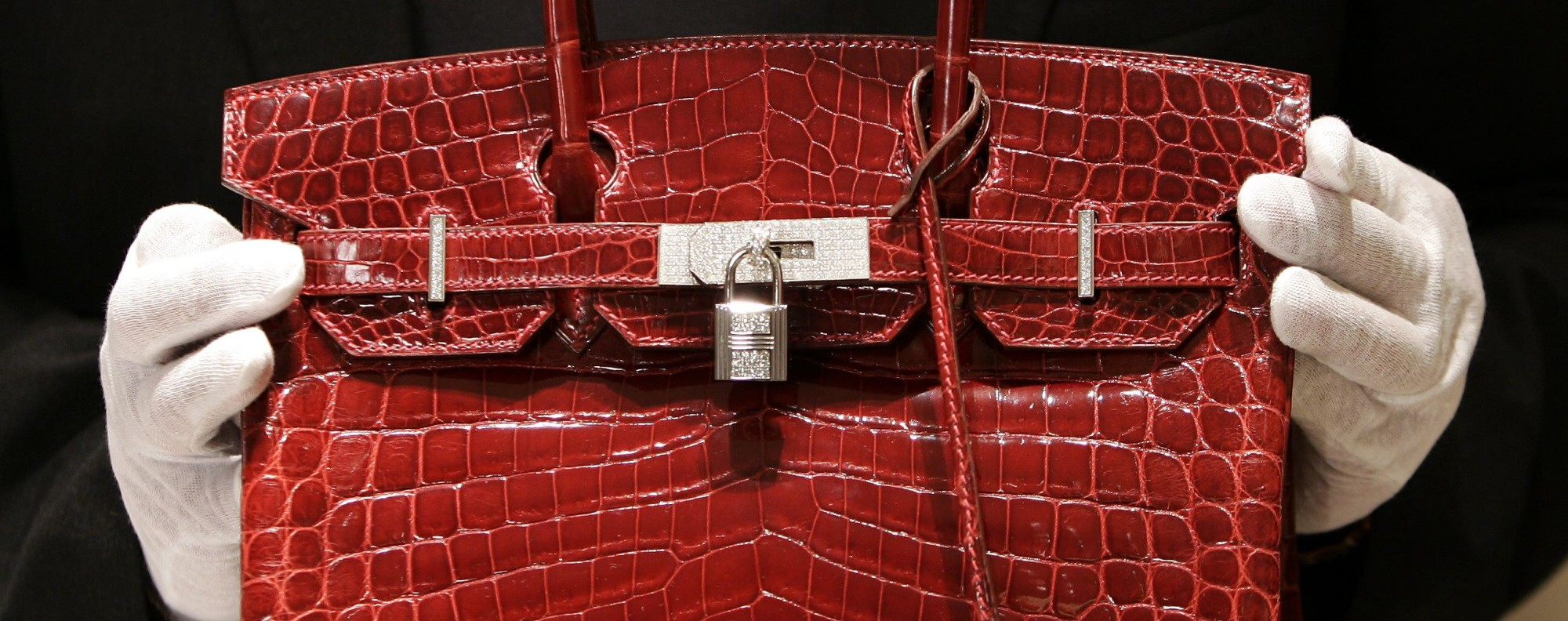 """An employee holding a 129,000 US$ crocodile-skin Hermes """"Birkin"""" bag during a private opening for the new Hermes store on Wall Street. Photo: AFP"""