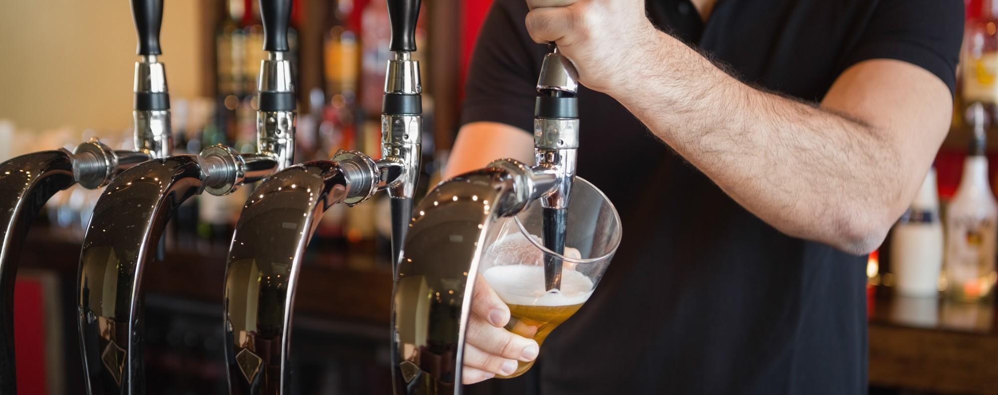 A bartender pulls a beer. Photo: Shutterstock