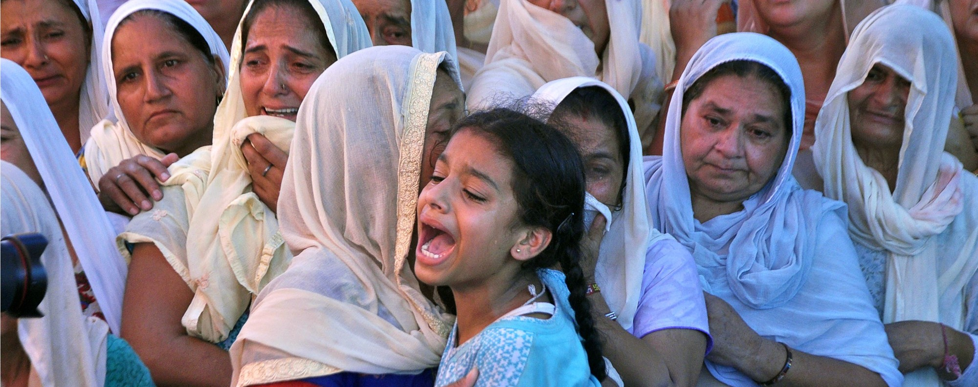 Daughter of a slain Indian soldier wails as the mortal remains of her father are brought to her home in Burn village near Jammu. Two Indian soldiers were killed on July 12 by firing from across the Line of Control between India and Pakistan in Kashmir. Photo: AFP