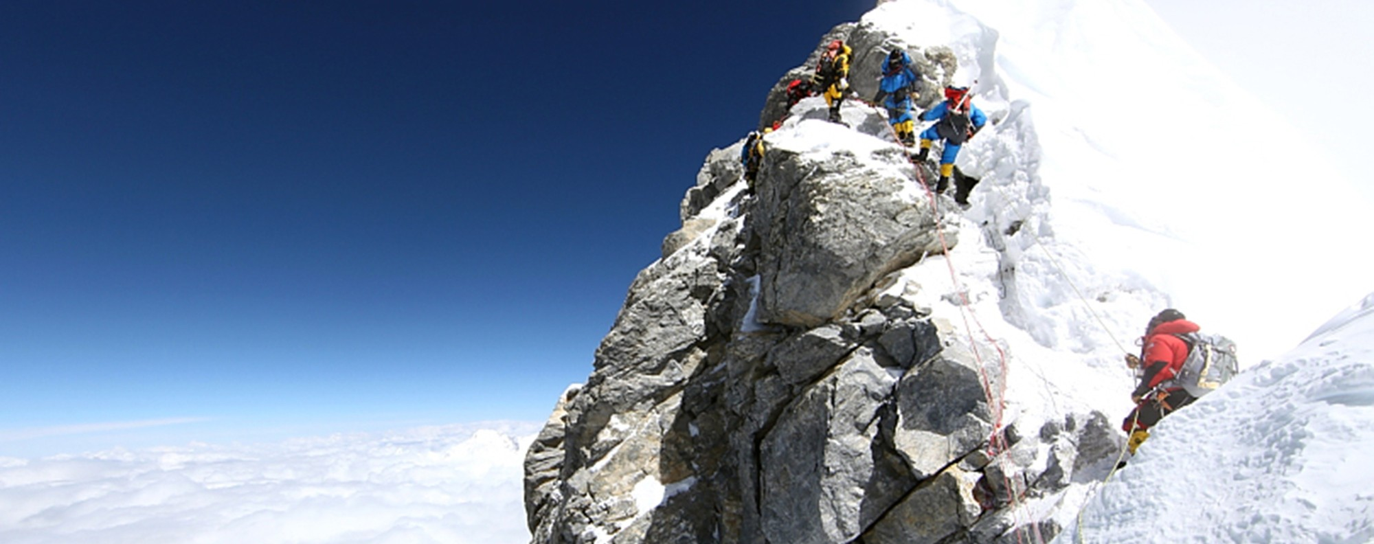 Mountaineers pass the Hillary Step heading for the summit of Everest.