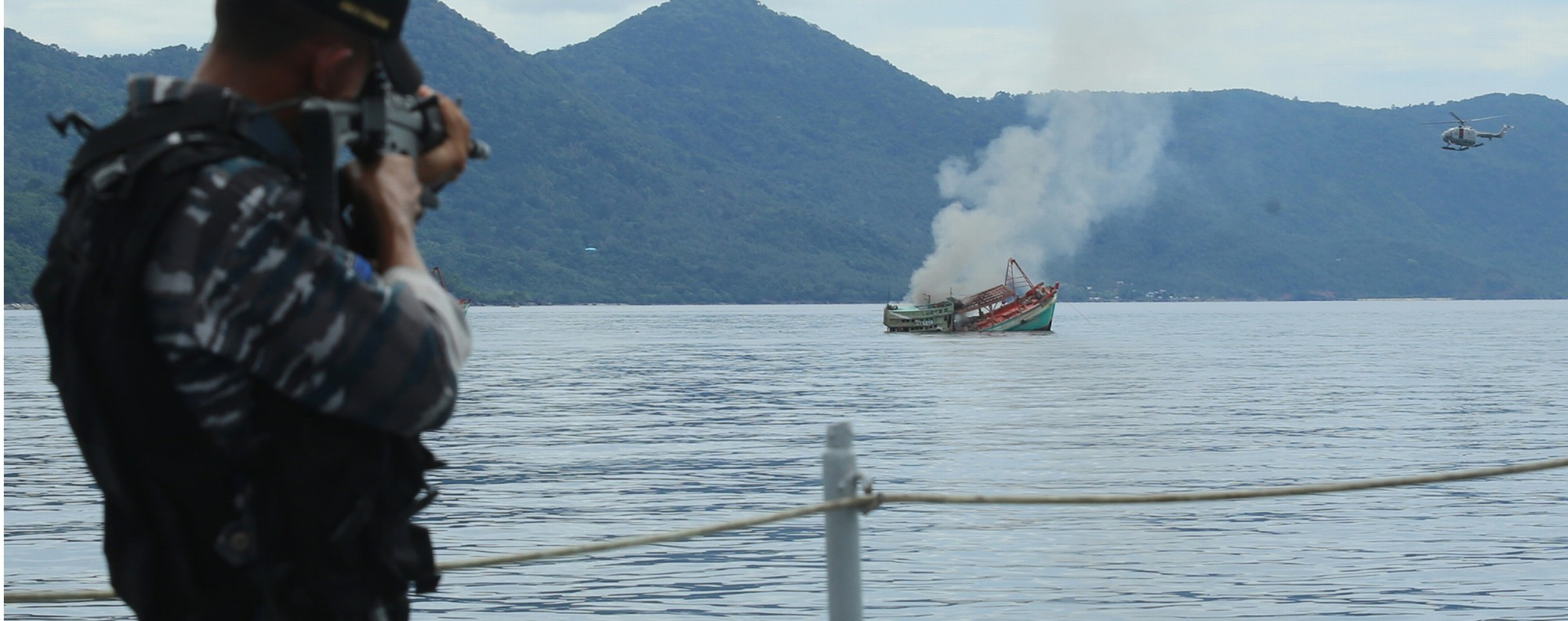 An Indonesian Navy officer takes aim at an illegal vessel. Photo: AFP
