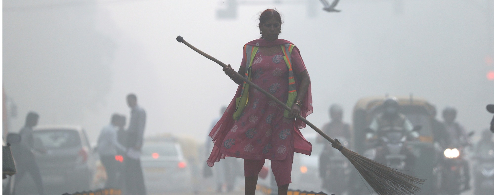 FILE PHOTO: A street cleaner works in heavy smog in Delhi, India, November 10, 2017. REUTERS/Cathal McNaughton/File Photo