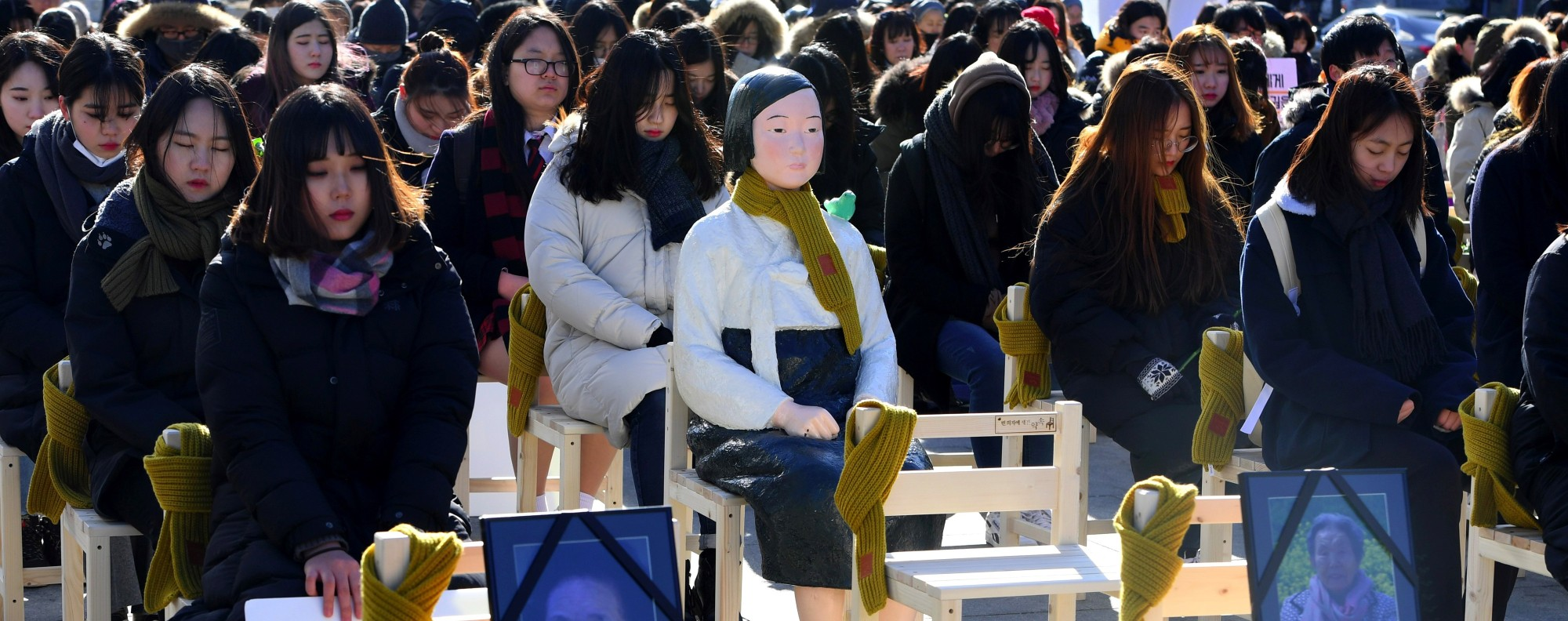 People sit around a statue of a comfort woman to commemorate the death of eight former sex slaves in 2017. Picture: AFP