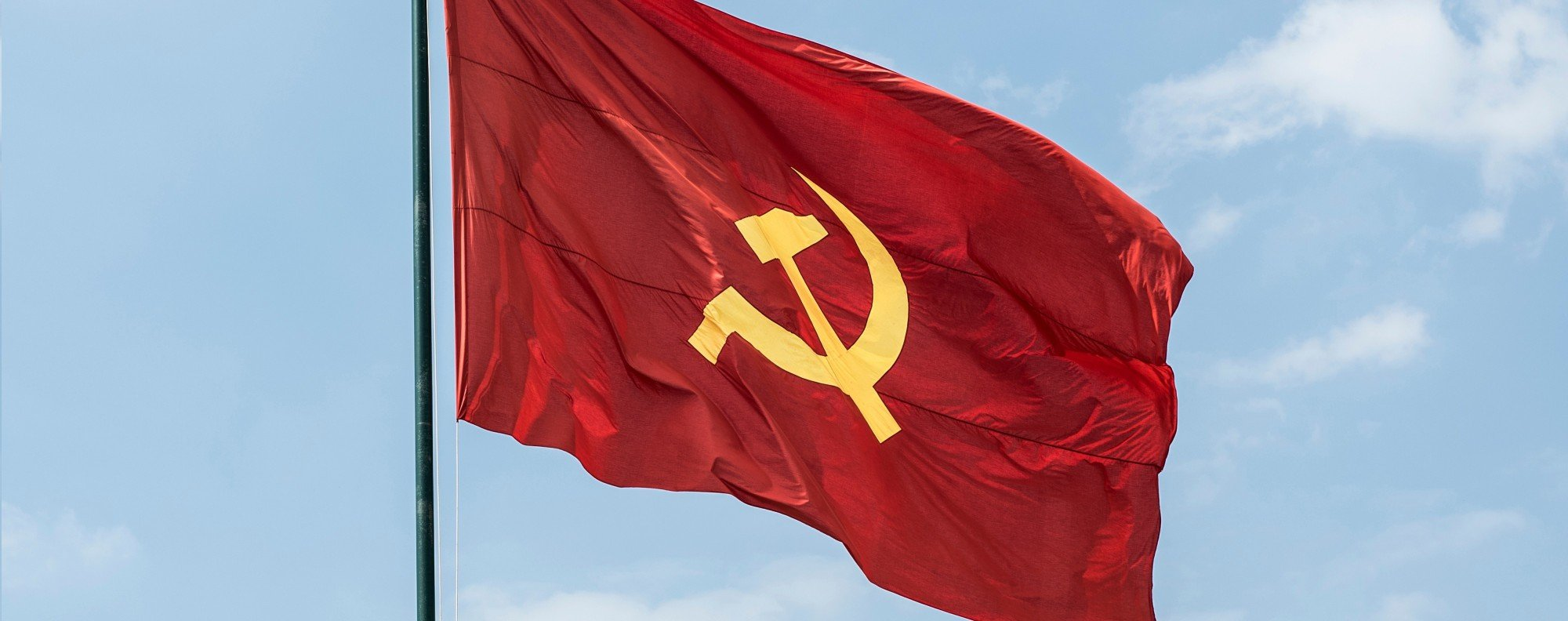 A hammer and sickle flag flies in the wind.