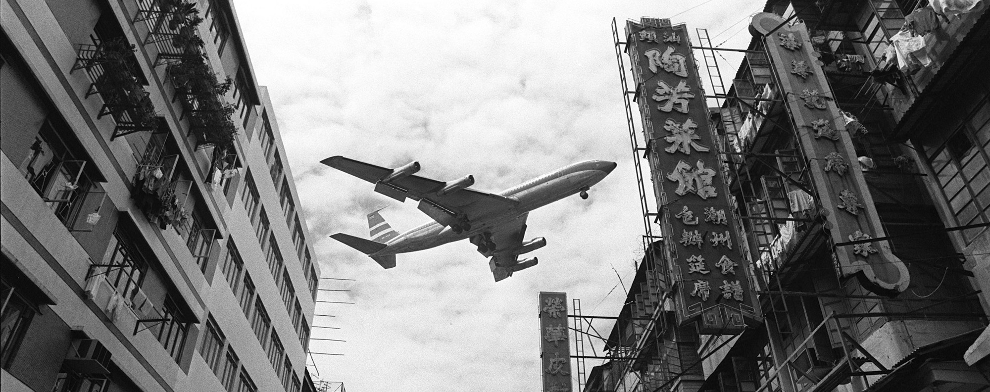A Cathay Pacific plane flies over low-rise buildings in Kowloon City. Picture: SCMP