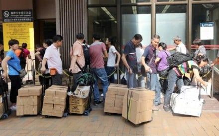 Parallel traders are seen outside Sheung Shui MTR station with their goods. Photo: David Wong
