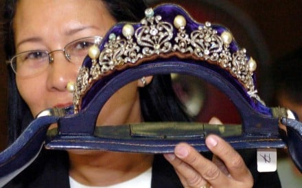 A government official holds a tiara inlaid with diamonds and South Sea pearls from one of the Imelda Marcos collections. Photo: AFP