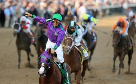 Jockey Victor Espinoza celebrates atop of California Chrome after crossing the finish line to win the 140th running of the Kentucky Derby in Louisville, Kentucky. Photo: AFP