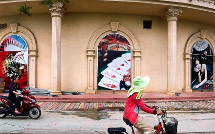 An employee rides a scooter past the Chinese-owned casino. Photo: AFP