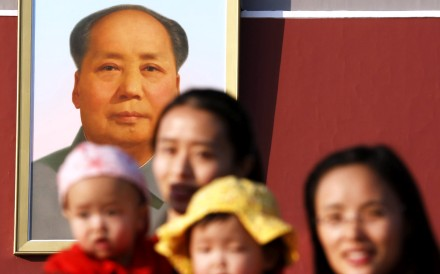 Two women and their babies pose for photographs in front of the giant portrait of late Chinese chairman Mao Zedong at the Tiananmen Gate in Beijing. Photo: Reuters