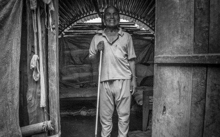 CHAUTARA, NEPAL - JULY 08: 57-year-old Tul Bahadur Shrestha stands at the entrance to his temporary shelter on July 08, 2015 in Chautara, Nepal. Tul has been blind since 4 years ago. The past 25th of April, he was living in a church that partially collapsed. Since then, he and his also disabled wife live in a temporary shelter in a very remote area where he is completely dependent on the help of others. Photo by Omar Havana