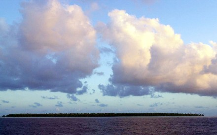 FILE - In this Dec. 30, 1999 file photo, clouds float over the Millennium Island, Kiribati, in the South Pacific. A man from one of the lowest-lying nations on Earth is trying to convince New Zealand judges that he's a refugee - suffering not from persecution, but from climate change. The 37-year-old and his wife left his remote atoll in the Pacific nation of Kiribati six years ago for higher ground and better prospects in New Zealand, where their three children were born. Immigration authorities have twice rejected his argument that rising sea levels make it too dangerous for him and his family to return to Kiribati. On Oct. 16, 2013, the man's lawyer, Michael Kidd, plans to argue the case before New Zealand's High Court. Kidd, who specializes in human rights cases, told The Associated Press he will appeal the case all the way to the country's Supreme Court if necessary.(AP Photo/Katsumi Kasahara, File)