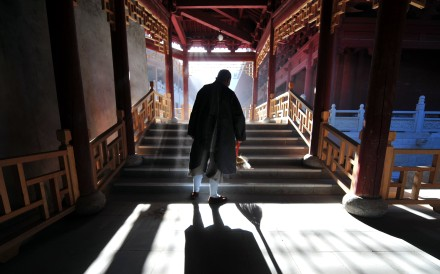 "To go with AFP story by Robert J. Saijet: CHINA-RELIGION-BUDDHISM A buddhist nun performs her morning chore of sweeping the floor at Wutaishan, literally ""Five Plateau Mountain"", on June 24, 2009, in northern China's Shanxi province. Considered the most holy land in Chinese Buddhism, Wutaishan is also one of the Four Sacred Mountains of Chinese Buddhism and believed to be home of the Bodhisattva of wisdom, Manjusri, or Wenshu in Chinese. Located in the mountains southwest of Beiijng at an average altitude of over 1,000 metres, Wutaishan's temples on the roof of northern China have for over a thousand years been a focal point of Buddhist pilgrimage for the Chinese, Tibetan, Mongol and Manchus. AFP PHOTO/Frederic J. BROWN"