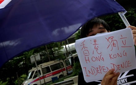 "A member of ""We are Hongkongers, Not Chinese"" waves the colonial Hong Kong flag outside the central government's liason office in Western district on October 1, 2012. Picture: Dickson Lee"