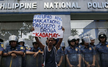A Filipino human rights advocate holds a placard as he joins a demonstration in front of the Philippine National Police (PNP) headquarters, protesting the alarming number of deaths related to government's war against illegal drugs, in Quezon city, east of Manila. Photo: EPA