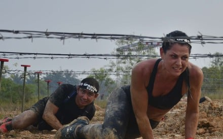 Nataile Dau, 44, crawling under barbed wire at Spartan Race Malaysia. She eventually finished third.