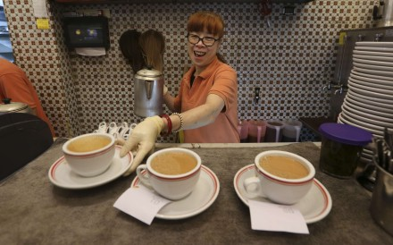 A woman serves up milk tea at a cha chaan teng in Happy Valley. Photo: Nora Tam