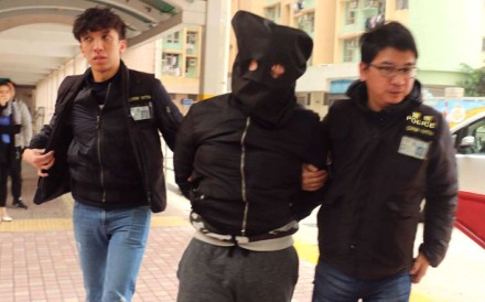One of the two arrested men is escorted to his Kwai Chung home for a house search. Photo: Handout