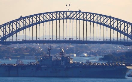 The USS Bonhomme Richard amphibious assault ship manoeuvres into port in front of the Sydney Harbour Bridge. Photo: Reuters