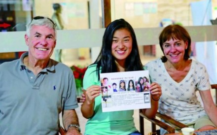 The girl, identified only as Lily and pictured with her parents, holds a leaflet appealing for information about her original family. Photo: Handout