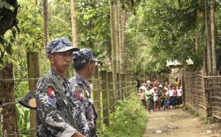Myanmar's Border Guard Police officers stand guard at a village street as some residents stand together in Yinmar Chaung Taung village of northern Buthidaung township where the majority Rohingya Muslims and some Rakhine Buddhists live in Rakhine state. Photo: AP