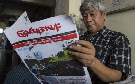 A newspaper being read by one of Myanmar's most famous cartoonists, Win Naing. Photo: AFP