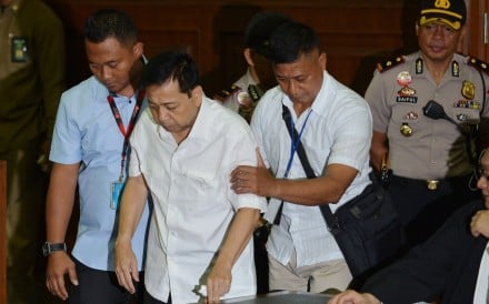 Former Indonesian parliament speaker Setya Novanto is escorted into a courtroom for his first trial in Jakarta. Photo: Reuters