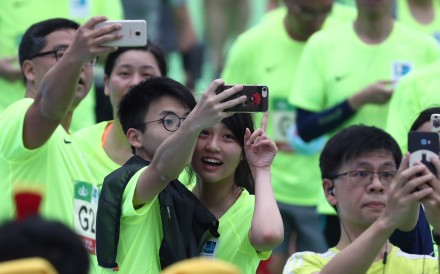 Runners take selfies at the Hong Kong Marathon finish line in Victoria Park. Photo: Nora Tam