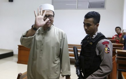 Suspected Indonesian militant Zainal Anshori waves to journalist during his sentencing hearing at East Jakarta District Court on Monday, February 12, 2018. Photo: AP