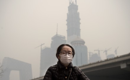A file picture of a woman cycling in heavy smog in Beijing. Photo: Agence France-Presse