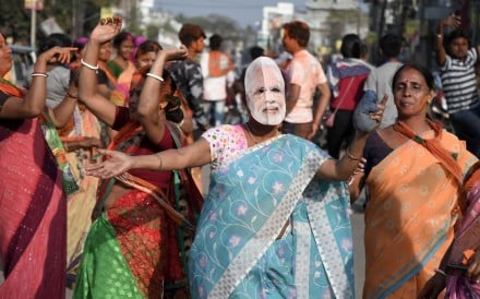 A BJP supporter wearing a Narendra Modi mask celebrates after victory against the Communist Party of India (Marxist) in Tripura state. Photo: EPA