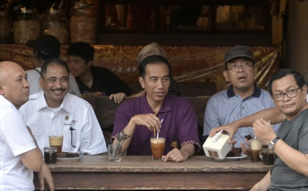 Indonesia President Joko Widodo (centre) sits with his ministers while visiting a cafe in Kuta beach, Bali. Indonesians could be jailed for criticising national politicians under a new law that came into force on Thursday. Photo: Reuters