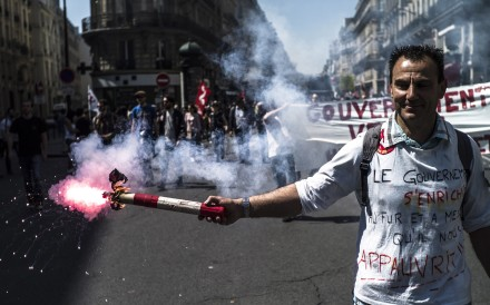 A protester lights a flare during a demonstration against the policies of French President Emmanuel Macron on Saturday. Photo: EPA-EFE