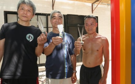 Players of popular lunchtime shuttlecock game (From left) Ah Wing, Tommy Tse and Chan Hung-fat with an artwork that some say has obstructed their space. Photo: Edmond So