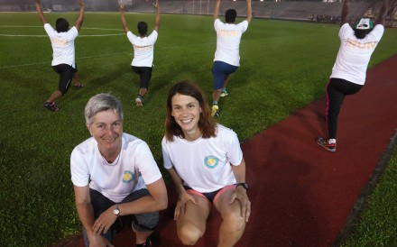 Brenda Sawyer, Run co-founder and Virginie Goethals, Run's programme head and director, with refugees at the Aberdeen Sports Ground. Photo: Jonathan Wong