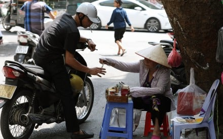 A woman sells cigarettes to a man on a street in Hanoi, Vietnam. Photo: EPA