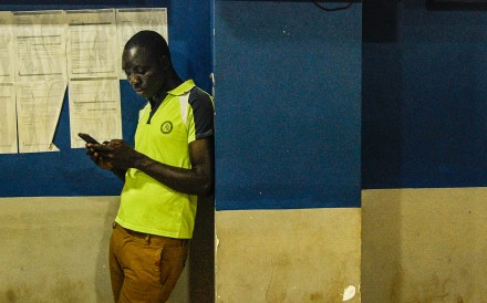 A Ugandan man looking at his mobile phone in a shop in Kampala. Photo: AFP