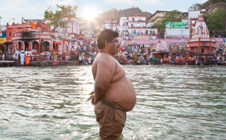 An overweight man stands in the River Ganges in India. While obesity can cause many diseases, it can be seen as a chronic illness in itself. Photo: Alamy