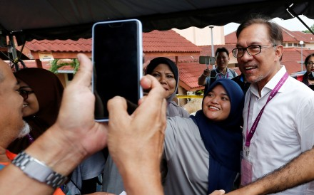 Anwar Ibrahim takes a photo with supporters as he visits a polling station. Photo: Reuters