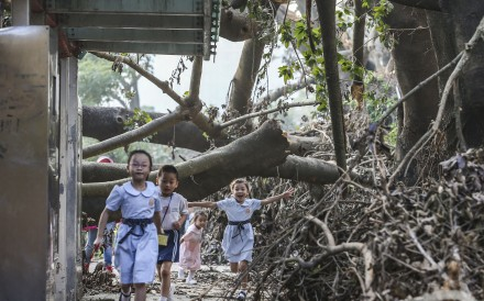 Children walk under collapsed trees along Tin Ping Road in Sheung Shui after Typhoon Mangkhut. Photo: Sam Tsang