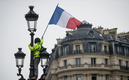 A protester wearing a yellow vest at the place de l'Opera in Paris The movement originally started as a protest about planned fuel hikes but has morphed into a mass protest against Macron's policies. Photo: AFP