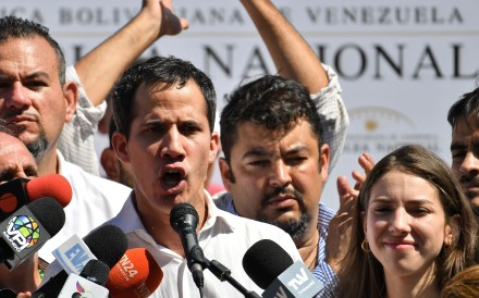 Venezuela's National Assembly president Juan Guaido, accompanied by his wife Fabiana Rosales gestures before a crowd of opposition supporters during an open meeting in Caraballeda, Vargas State, Venezuela, on January 13, 2019. Photo: AFP