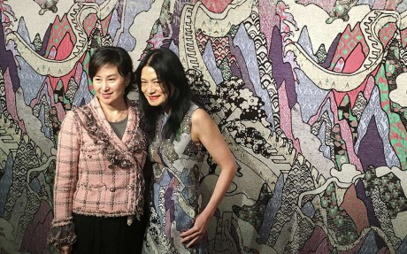 Pansy Ho (left) stands next to Hong Kong fashion designer Vivienne Tam, who designed the tapestry behind her called Cultural Dreamland. Photo: Vivienne Chow
