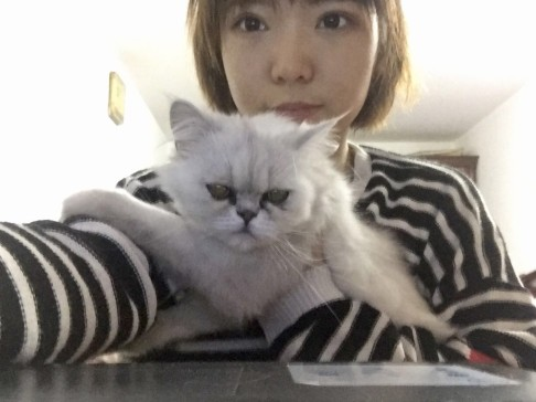 Shen Xiaojie and her cat Kimi pose for a selfie.
