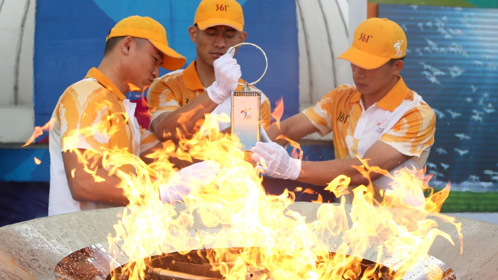 Flame guards light the lantern from the cauldron during the 2nd Asian Youth  Games flame-lighting ceremony in Nanjing, capital city of Jiangsu. Photo:  Xinhua