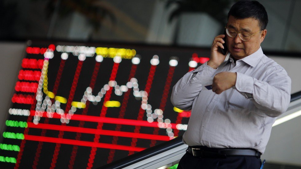 A man talks on his cell phone inside the Shanghai Stock Exchange building  in the city's Pudong financial district. Chinese markets open mixed as  punters ...
