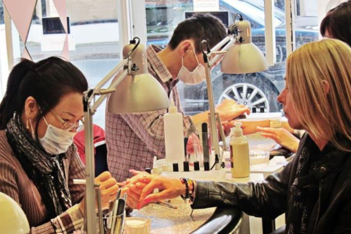 Vietnamese manicurists work in a nail salon in Stratford-upon-Avon, in the British Midlands.